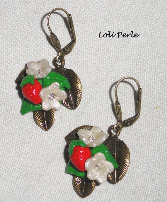 Boucles d'oreilles fraises rouges avec petites fleurs en argile sur feuillage bronze