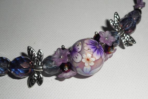 Collier perle fleurie violet avec perles en cristal sur cordon en coton ciré
