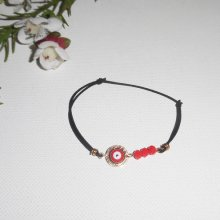 Bracelet  plaqué or avec oeil et perles en cristal rouge sur cordon noir élastique réglable